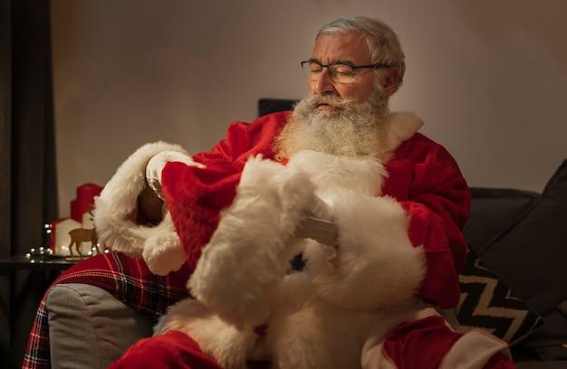 Nahaufnahme weihnachtsmann, der weihnachtshut hält