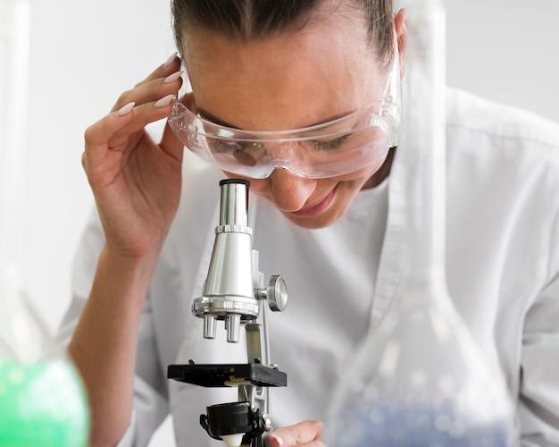 Nahaufnahme-wissenschaftsfrau mit mikroskop