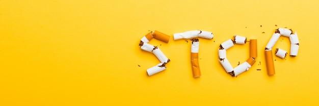 Nahaufnahme wort stop buchstabiert text der stapel zigarette oder tabak