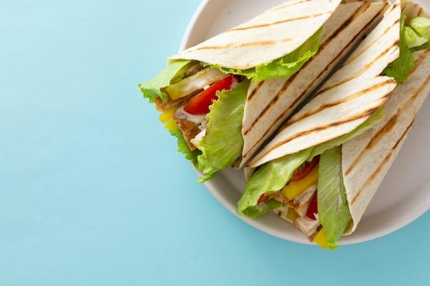 Nahaufnahme wrap burrito sandwich mit fladenbrot mit gemüse und weißem fleisch. platz kopieren