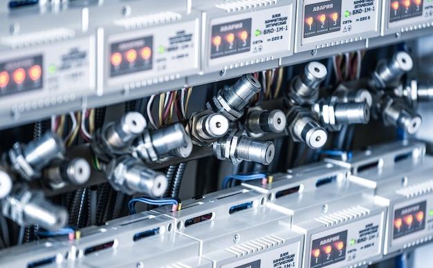 Nahaufnahme zahlreicher metallstecker hängen neben instrumententafeln in einer fabrik zur herstellung von spezialgeräten. industrielles fertigungskonzept