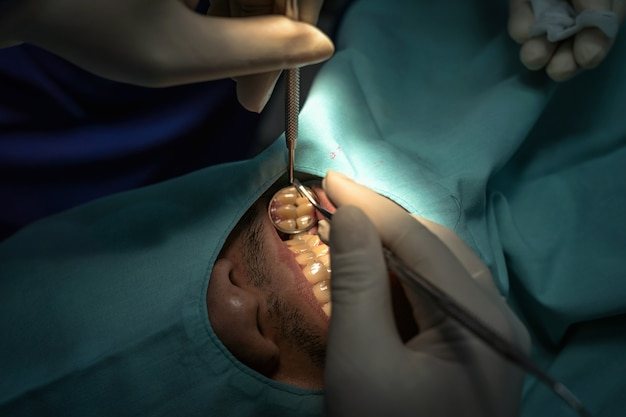 Nahaufnahme zahnarzt und assistent, die für die prüfung und die zähne säubern an der zahnmedizinischen klinik funktionieren