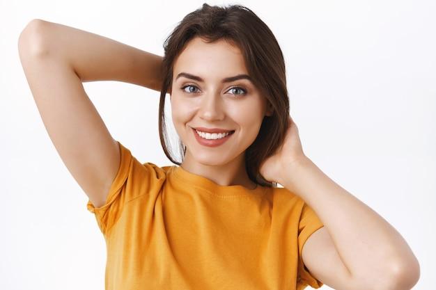 Nahaufnahme zarte, feminine verführerische junge stilvolle kaukasische frau in gelbem t-shirt, die hände hinter sich hält, um ihr haar zu flicken, zopf zu machen oder es zu bürsten, glücklich lächelnd, weißer hintergrund