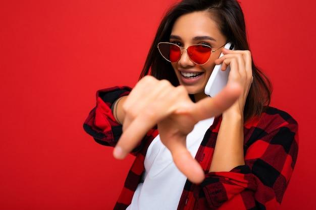 Nahaufnahme ziemlich glückliche junge brünette frau, die stilvolles rotes hemd weißes t-shirt und rot trägt