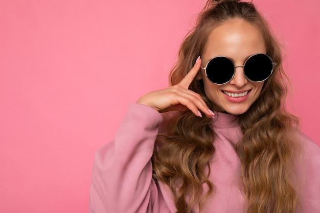 Nahaufnahme ziemlich positiv lächelnde junge blonde lockige frau isoliert über rosa hintergrundwand, die lässige rosa sportkleidung trägt