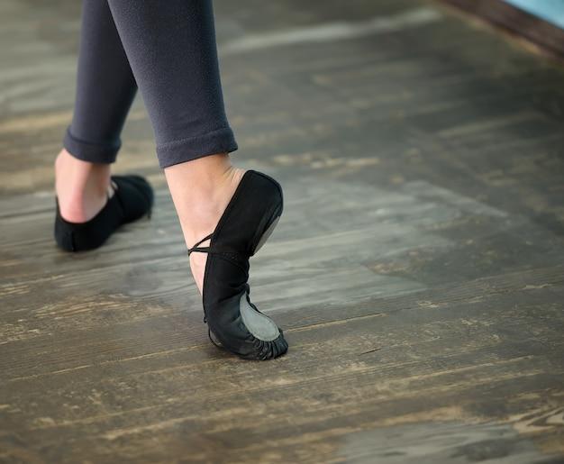 Nahaufnahme zu ballerinas beine in pointes auf holzboden
