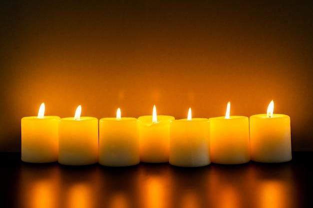 Nahaufnahme zu brennenden kerzen in der dunkelheit