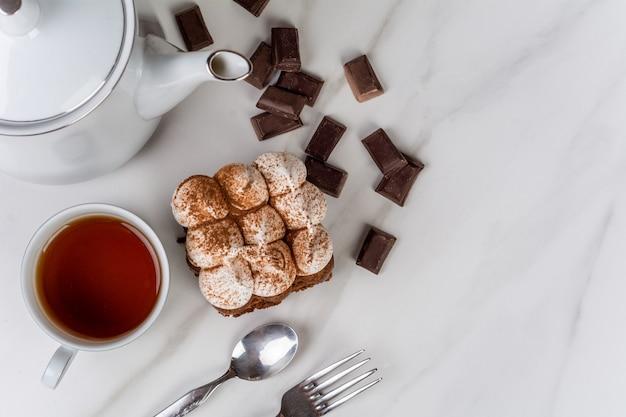 Nahaufnahme zu köstlichem mini-schokoladenkuchen mit einer tasse tee. koch- und bäckereikonzept.
