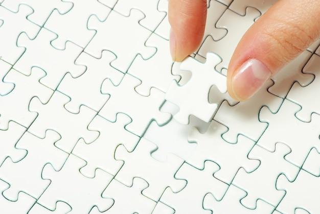 Nahaufnahme zur hand, die ein leeres puzzle macht