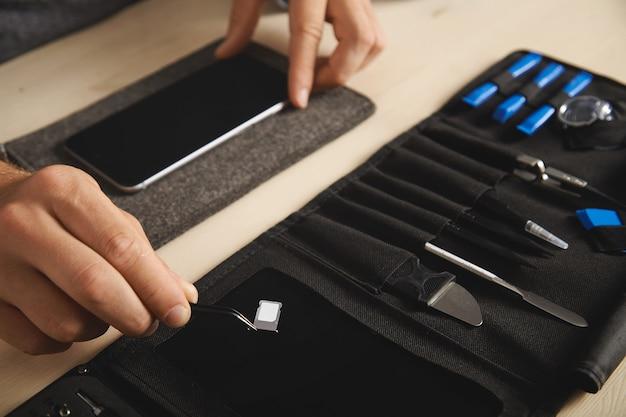 Nahaufnahme zur hand mit dem pincher-werkzeug, das den sim-kartensteckplatz mit nano-sim über der schwarzen magnetplatte auf einem tragbaren gerät für den elektronischen repirirment-service hält