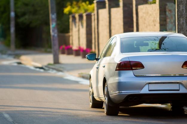 Nahaufnahme zurück von neuem glänzendem teurem silberauto, das entlang stadtstraße auf unscharfen bäumen, autos und gebäudehintergrund am sonnigen sommertag bewegt. komfortabler transport und geschwindigkeit im modernen leben.