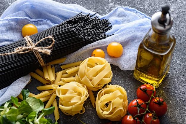 Nahaufnahme zutaten für abendessen-schwarze spaghetti auf pastell lila serviette, fettuccine, tomaten, maissalat, olivenöl auf grauem hintergrund
