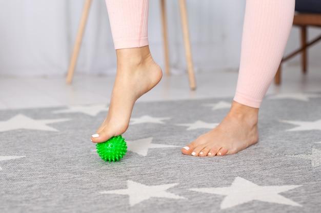 Nahaufnahme zwei anmutige füße einer jungen frau, die auf einem grünen spiki-massageball steht