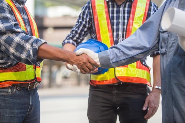 Nahaufnahme zwei ingenieure, die hand rütteln, nachdem ein geschäftstreffen beendet worden ist