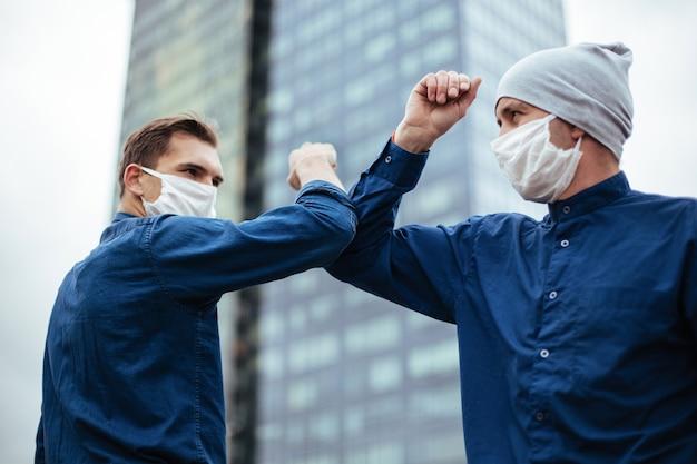 Nahaufnahme. zwei junge männer grüßen sich mit den ellbogen. konzept des gesundheitsschutzes