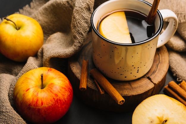 Nahaufnahmeäpfel und -gewebe nahe gewürztem getränk