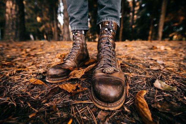 Nahaufnahmeansicht an den männlichen beinen in den vintage-lederstiefeln im herbstpark