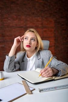 Nahaufnahmeansicht denkend weiblicher ingenieur, der hinter ihrem arbeitsplatz sitzt