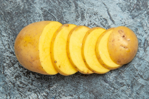 Nahaufnahmeansicht der einfachen köstlichen ungeschälten kartoffelscheiben auf grauem tisch