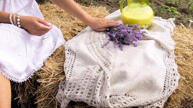 Nahaufnahmeansicht der frau, die auf heuhaufen sitzt und lavendelblumenblumenstrauß hält.