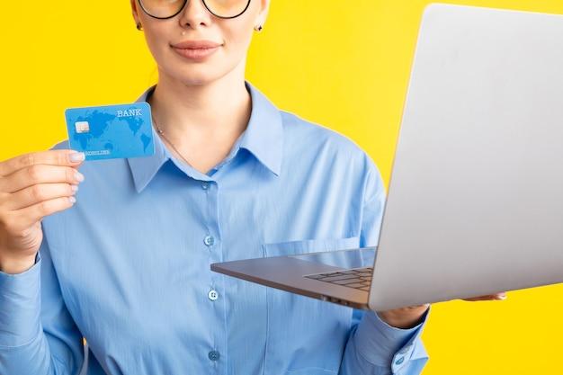 Nahaufnahmeansicht der frau im blauen stoß, der laptop und kreditkarte auf gelb hält