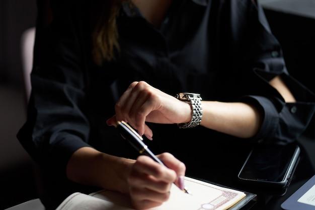 Nahaufnahmeansicht der frauenarmbanduhr auf der hand des mädchens.