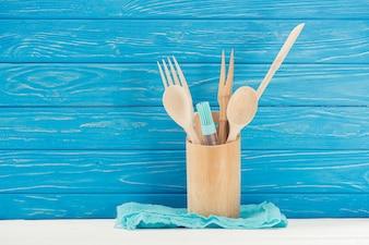 Nahaufnahmeansicht des Lappens, der Gebäckbürste und der Küchengeräte vor blauer hölzerner Wand