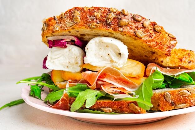 Nahaufnahmeansicht eines feinschmeckerischen parmaschinken-, mozzarella- und pfirsichsandwiches auf einer platte