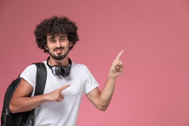 Nahaufnahmeansicht junger mann, der mit kopfhörer oben zeigt