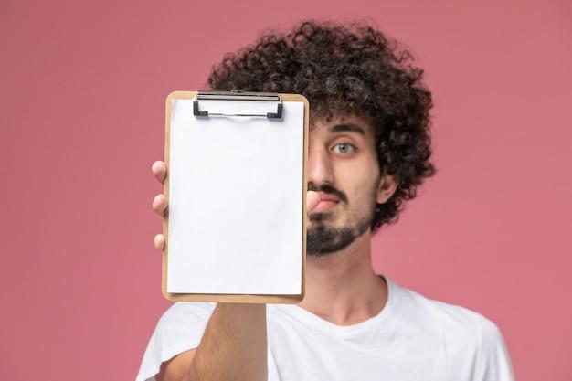 Nahaufnahmeansicht junger mann, der sein büro-notizbuch zur kamera zeigt