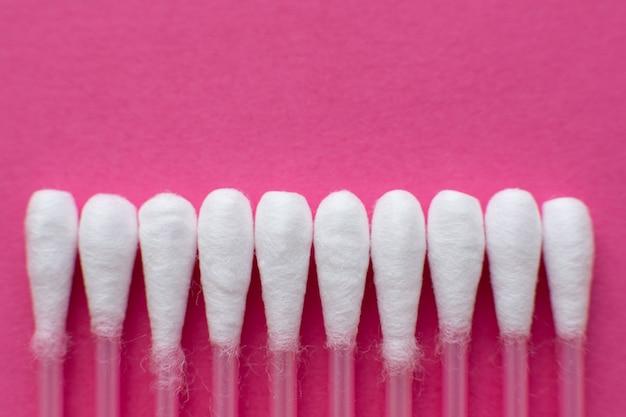 Nahaufnahmeansicht von oben genanntem auf köpfen von den baumwollknospen gelegt in eine horizontale linie auf rosa hintergrund