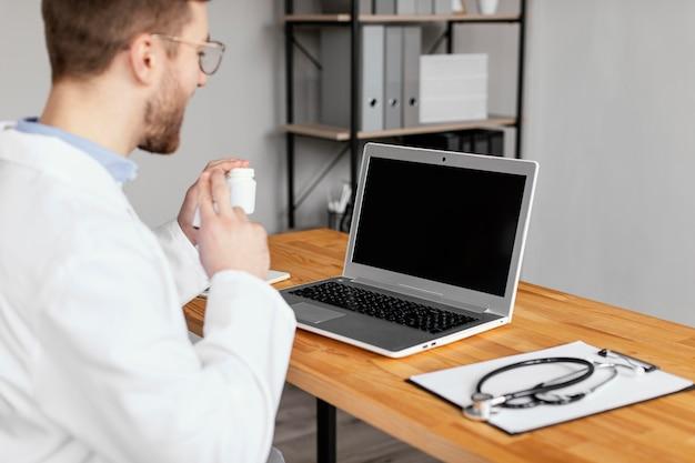 Nahaufnahmearzt, der mit laptop arbeitet