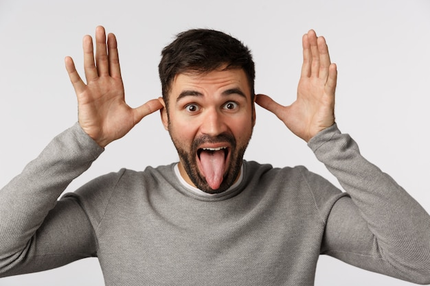 Nahaufnahmeatelieraufnahme sorgloser und spielerischer, lustiger netter bärtiger mann in der grauen strickjacke, stockzunge und machen neckende geste mit den händen nahe ohren, täuschen herum und bitten, ihn zu fangen, mit kindern zu spielen