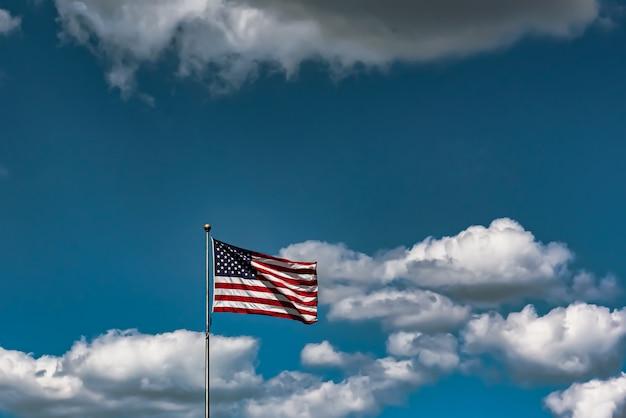 Nahaufnahmeaufnahme der amerikanischen flagge, die in der luft unter einem bewölkten himmel weht