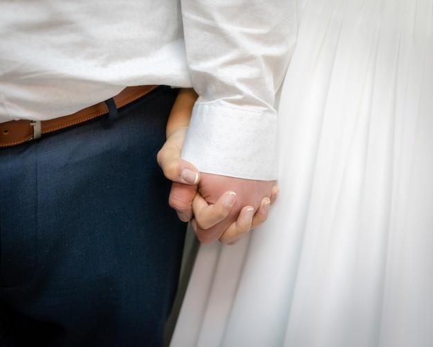 Nahaufnahmeaufnahme der braut und des bräutigams, die die hände voneinander halten