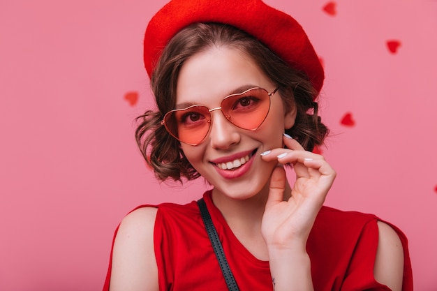 Nahaufnahmeaufnahme der erfreuten kaukasischen frau in der herzbrille, die mit fröhlichem lächeln aufwirft. ansprechendes französisches weibliches modell, das glück ausdrückt.