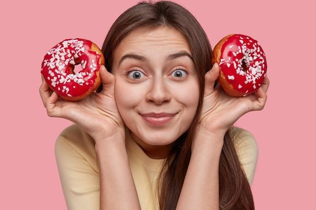 Nahaufnahmeaufnahme der erfreuten schönen frau hat dunkles haar, hält zwei rote donuts mit streuseln
