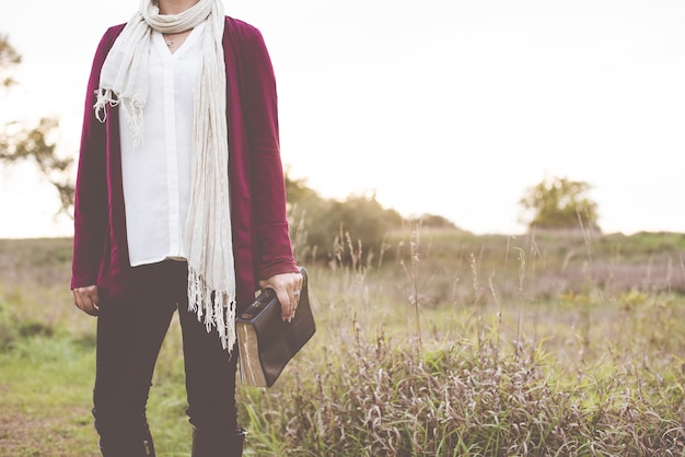 Nahaufnahmeaufnahme der frau, die in einem grasfeld steht, während die bibel mit unscharfem hintergrund hält