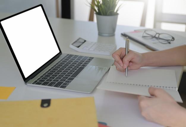 Nahaufnahmeaufnahme der frau, die notizen und muckup-laptop des leeren bildschirms schreibt, der auf den tisch gelegt wird.