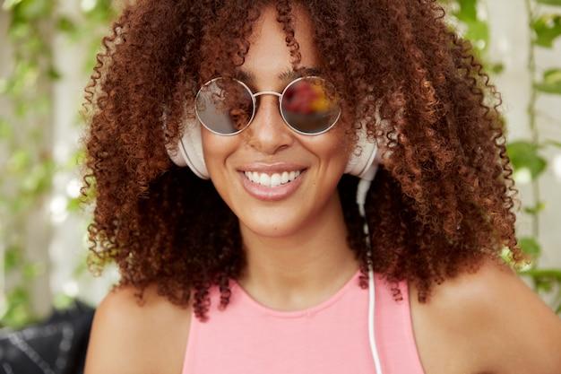 Nahaufnahmeaufnahme der fröhlichen afroamerikanischen bloggerin genießt radiosendung, verbunden mit nicht erkennbarem elektronischem gerät, hat ein breites lächeln und weiße perfekte zähne. menschen- und hobbykonzept