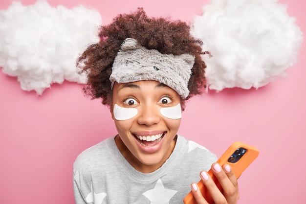 Nahaufnahmeaufnahme der fröhlichen afroamerikanischen frau in der schlafmaske und im pyjama schaut gern in die kamera, die handy-creat-post für ihren blog verwendet, trägt kollagenflecken unter augenposen über wolken