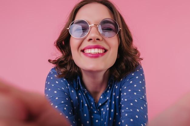 Nahaufnahmeaufnahme der fröhlichen jungen frau in der lila sonnenbrille, die mit geschlossenen augen lacht. porträt des freudigen lockigen mädchens in der blauen bluse, die selfie mit lächeln macht.