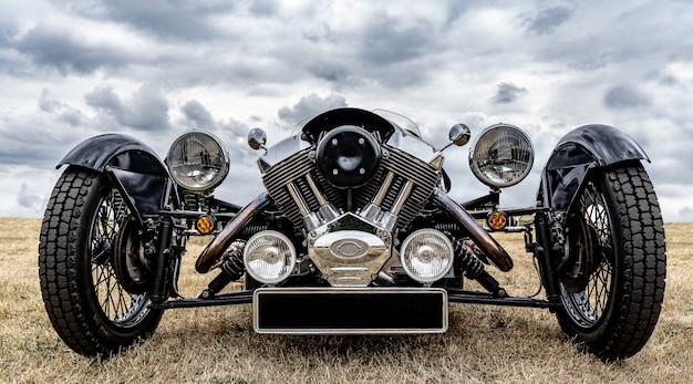 Nahaufnahmeaufnahme der front eines schwarzen fahrzeugs, das auf einem trockenen feld unter einem bewölkten himmel geparkt wird