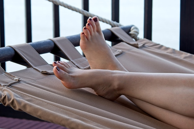 Nahaufnahmeaufnahme der füße einer person beim ausruhen auf einer hängematte in strandnähe