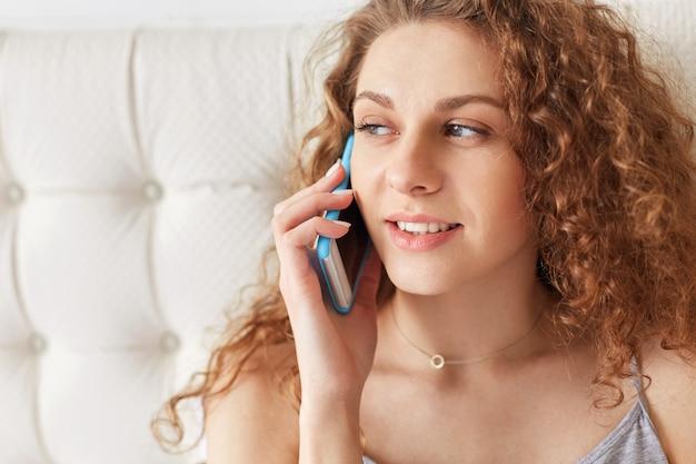 Nahaufnahmeaufnahme der gut aussehenden lockigen frau mit gesunder reiner haut, hat telefongespräch über smartphone, schaut nachdenklich beiseite, spricht mit freund während der freizeit. menschen und lebensstil