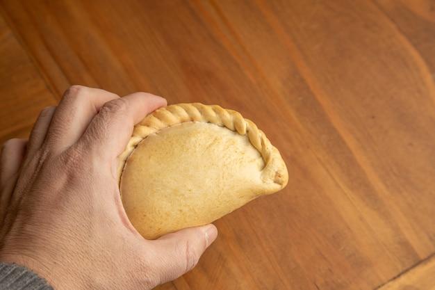 Nahaufnahmeaufnahme der hand einer person, die einen selbst gemachten köstlichen knödel hält