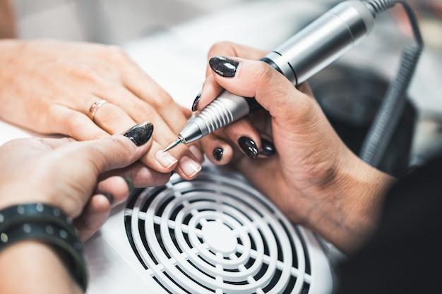 Nahaufnahmeaufnahme der hardware-maniküre in einem schönheitssalon. manikürist wendet elektrische nagelfeilenbohrmaschine auf maniküre an weiblichen fingern an.