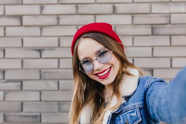 Nahaufnahmeaufnahme der lachenden wunderbaren frau mit den roten lippen, die foto von sich selbst machen. romantisches weißes mädchen, das selfie im kalten frühlingstag macht und lächelt.