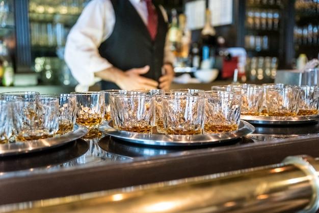 Nahaufnahmeaufnahme der mit whisky gefüllten gläser an der bar