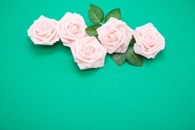 Nahaufnahmeaufnahme der rosa rosen lokalisiert auf einem grünen hintergrund mit kopienraum